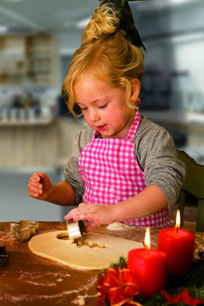 Ein kleines Kind bei mBacken von Kekse und Plätzchen zu Weihnachten